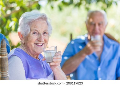 Aged couple is sitting under a tree in garden drinking a lemonade