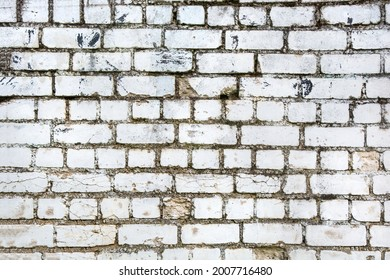 aged cracked horizontal white brick wall with moss