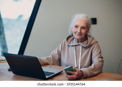 Aged elderly woman with laptop and mobile phone working on computer at table