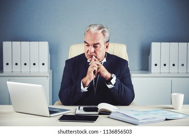 Aged elegant male with grey hair in dark business suit sitting at office desk with important documents and looking attentively at laptop with folded hands