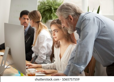 Aged executive manager boss checking work of young trainee looking at computer screen in office with multiracial people, senior mentor teaching training female intern, supervising or teamwork concept