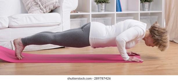 Aged exercising woman during yoga sun salutation