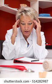 aged female doctor with headache, maybe burnout, documents on a table, red office