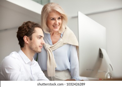 Aged female mentor boss smiling looking at computer screen happy for achievement and good online work result of young male intern, senior woman executive leader supervising teaching helping colleague