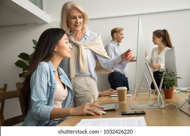 Aged female mentor training young asian intern explaining computer work, senior friendly executive teaching new employee looking at pc screen, older teacher talks to student helping with online task