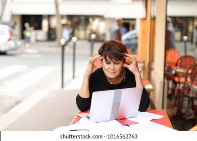 aged female screenwriter sitting in outdoor cafe and reproduce scenario from paper drafts in text file on laptop. Lady dressed in black cardigan looks like very pleased with work. Woman scans p