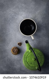 Aged Fermented Pu erh Tea in Citrus Peel Green Kettle Empty Cup on Dark Stone Background. Chinese Japanese Asian Cuisine. Healthy Drinks Detox Antioxidants Concept. Minimalist Flat Lay with Copy Space