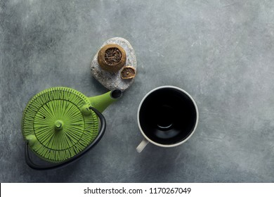 Aged Fermented Pu-erh Tea in Citrus Peel Green Kettle Empty Cup on Dark Stone Background. Chinese Japanese Asian Cuisine. Healthy Drinks Detox Antioxidants Concept. Vintage Minimalist Flat Lay