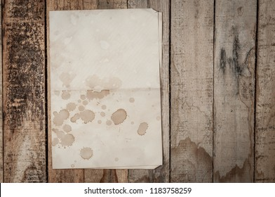 Aged folded letter on old wood table. Vintage Crumpled paper texture on wooden table. Paper with wine stain or coffee spot