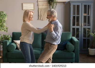 Aged funny laughing wife and husband holds hands standing in living room listening rhythmic music favourite song dancing enjoy weekend, spouses celebrate anniversary romantic date feels happy concept