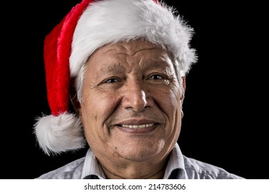 Aged gentleman, wearing a red and white Old Father Christmas hat, is smiling. Bright teeth are showing. Black background. Focus on eyes. Ample depth of field. Seasonal theme.