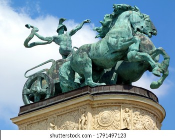 aged green bronze statue of man with snake on a chariot. the symbol of war. Heroes' square in Budapest, Hungary.   blue summer sky. low angle view. travel and tourism concept. beautifully carved base.