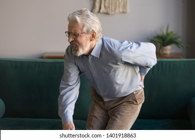 Aged grey haired sixty years man in glasses writhes in pain suffers from low back strain, touch rubbing or massaging loin reduces backache. Degenerative disk disease, pinched nerve rheumatism concept