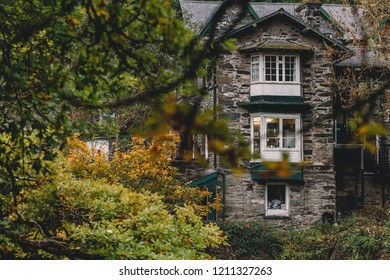 Aged grey stone house in the colorful autumn forest village,