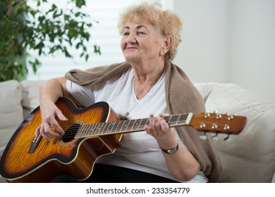 Aged happy woman playing the guitar in her room