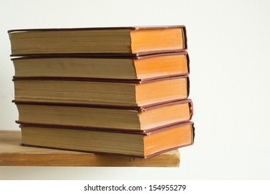 aged hardcover books stack on bookshelf