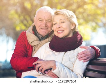 Aged husband and wife sitting together on bench in park on chilly day