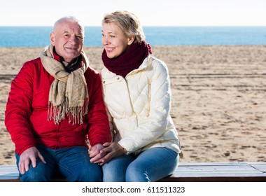 Aged husband and wife sitting together on bench by sea on chilly day