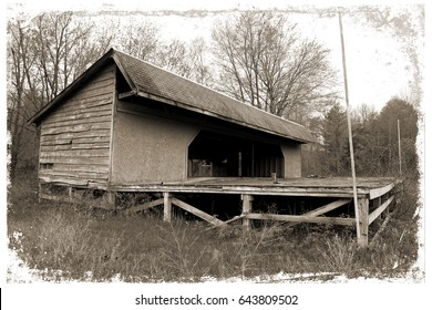 Aged image of an abandoned structure in the woods. Weathered and distressed framing. Sepia tone.