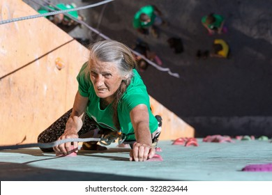 Aged Lady Doing Extreme Sport Elderly Female Makes Hard Move on Outdoor Climbing Wall Sporty Clothing on Fitness Training Intense but Positive Face Using Rope and Belaying Gear