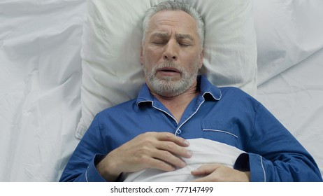 Aged male loudly snoring and puffing in bed, sleeping problems at old age