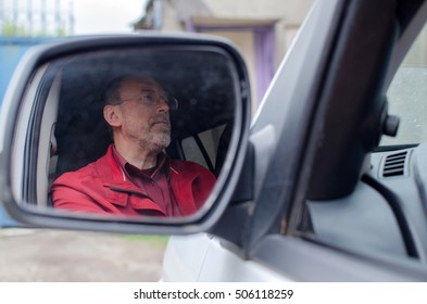 Aged man in the car on the street