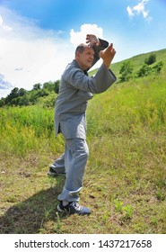 Aged man is engaged in martial arts in nature. Classes and master classes in kung fu, Tai Chi, qigong, multidimensional medicine, healthy lifestyle