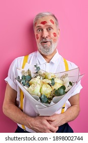 aged man with lipstick marks on face holding flowers as gift, stand in shock suprised by reaction by his girlfriend, anniversary present concept