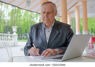 Aged man is making notes in the notebook in the park