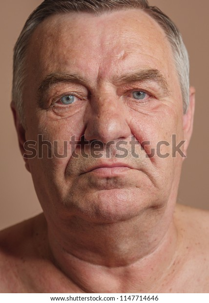 Aged man portrait on light background.