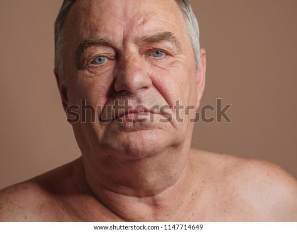 Aged man portrait on light background.