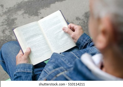 Aged man is reding the book in the park