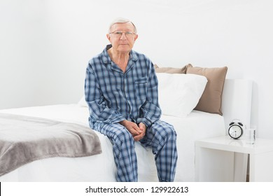 Aged man sitting on his bed in the bedroom