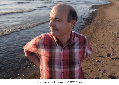 Aged man taking stroll alone on beach in summer season. He is looking aside