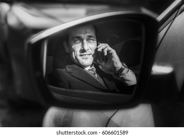 Aged man talking on phone in drivers seat,  view in mirror