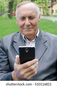 Aged man is using his cellphone in the park