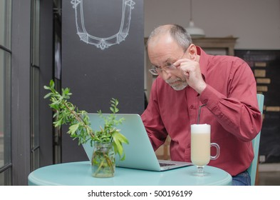 Aged man using his laptop on the table