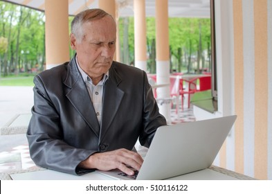 Aged man is using laptop in the park