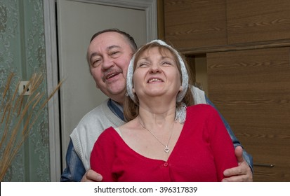 Aged man in white knitted vest is embracing his smiling girlfriend in bright red blouse with a neckline putting his hands to her arms.