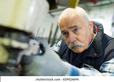aged man working in an industrial factory