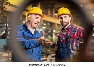 Aged master and his trainee in workwear and protective helmets consulting about new industrial machine equipment in workshop