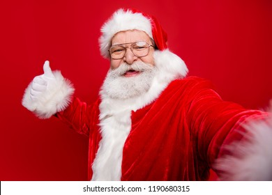 Aged mature stylish grandfather Santa Claus with white beard in costume headwear gloves stylish spectacles show like sign thumb up take picture on camera of smartphone isolated on red background