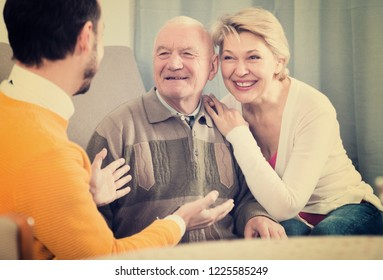 Aged parents and adult son enjoying quiet evening together at home