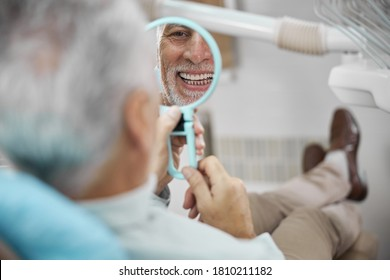 Aged patient sitting in a dental chair while looking at himself in the mirror