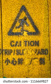 Aged and peeled Caution Trip Slip Hazards sign painted on yellow wall.