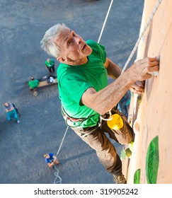 Aged Person Practicing Extreme Sport Elderly Male Climber Makes Hard Move Looking High Up on Outdoor Climbing Wall Sport Competitions Very Emotional Face Belaying Partner Fans Staying on Remote Ground