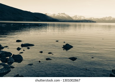Aged photo effect Lake Tekapo sunsise over rocky foreshore and low water level of calm peaceful lake to distant Soutern Alps.