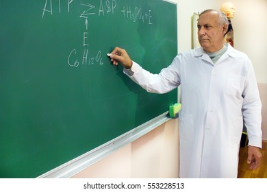 Aged professor writing on the blackboard with chalk