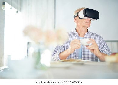 Aged restired man with cup of tea sitting by table and watching virtual webcast in vr goggles
