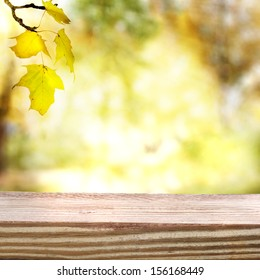 Aged and rustic wooden boards with an autumn sky and foliage background